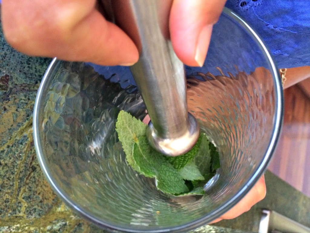 Muddling the lime, sugar and mint.